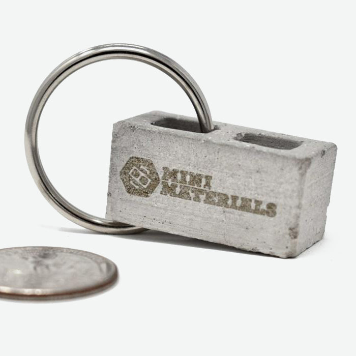 this is a 1:12 scale mini cinder block with the Mini Materials logo engraved on one side. the mini cinder block has a silver colored metal key ring attached to it on the left side. a quarter is sitting on the left side of the cinder block to show scale