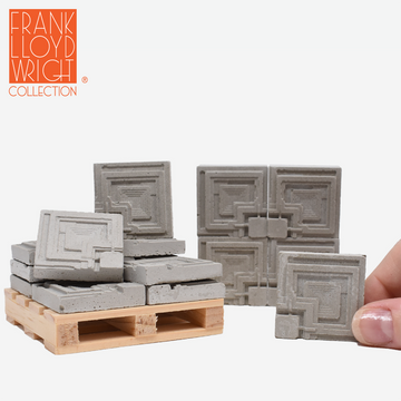 1:12 scale mini concrete textile blocks that mimic the frank lloyd wright ennis house textile blocks. some are sitting on a mini wood pallet. there are 4 mini textile blocks stacked up like a wall in the background and a hand is holding one of the textile blocks on the right side.