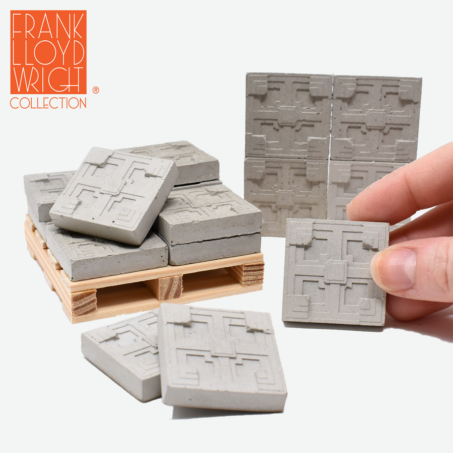 1:12 scale mini concrete textile blocks that mimic the frank lloyd wright storer house textile blocks. some are sitting on a mini wood pallet. there are 4 mini textile blocks stacked up like a wall in the background and a hand is holding one of the textile blocks on the right side.