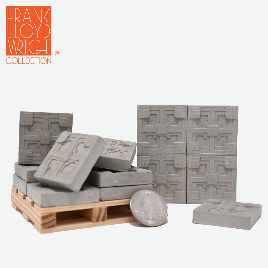 1:12 scale mini concrete textile blocks that mimic the frank lloyd wright storer house textile blocks. some are sitting on a mini wood pallet and have a quarter sitting in front to show scale.. there are 4 mini textile blocks stacked up like a wall.
