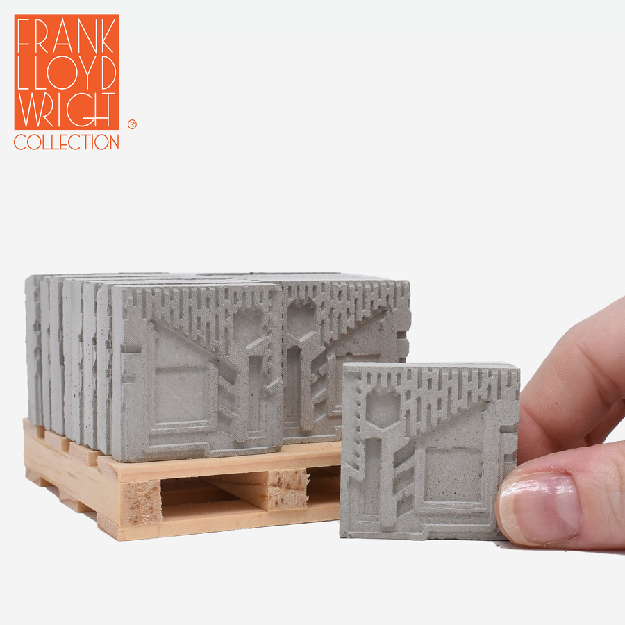 1:12 scale mini concrete textile blocks that mimic the frank lloyd wright freeman house textile blocks on a mini wood pallet with a hand holding one in front of the pallet to show scale.