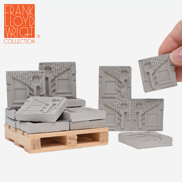 1:12 scale mini concrete textile blocks that mimic the frank lloyd wright freeman house textile blocks. some are sitting on a mini wood pallet and have a quarter sitting in front to show scale. there are 3 mini textile blocks stacked up like a wall and a hand is holding one of the textile blocks on the right side.