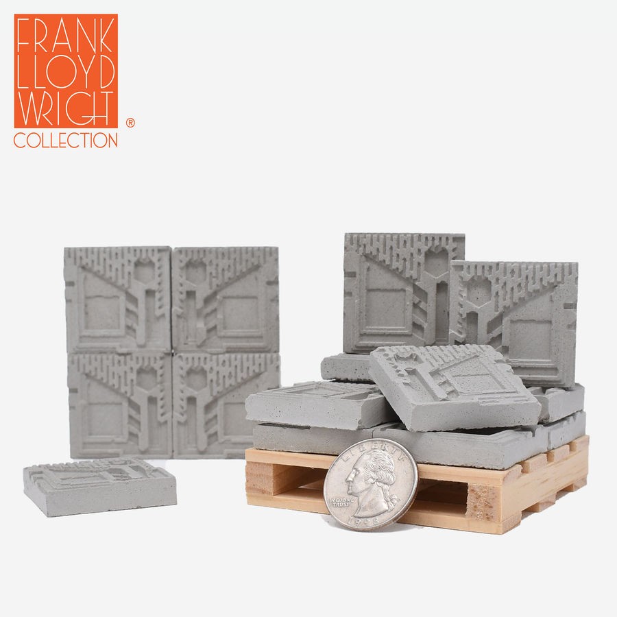 1:12 scale mini concrete textile blocks that mimic the frank lloyd wright freeman house textile blocks. some are sitting on a mini wood pallet and have a quarter sitting in front to show scale.. there are 4 mini textile blocks stacked up like a wall.