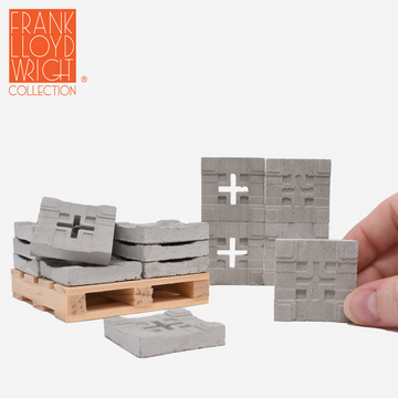 1:12 scale mini concrete textile blocks that mimic the frank lloyd wright storer house textile blocks. some are sitting on a mini wood pallet and have a quarter sitting in front to show scale. there are 4 mini textile blocks stacked up like a wall and a hand is holding a 5th block in front of the wall on the right side to show scale.