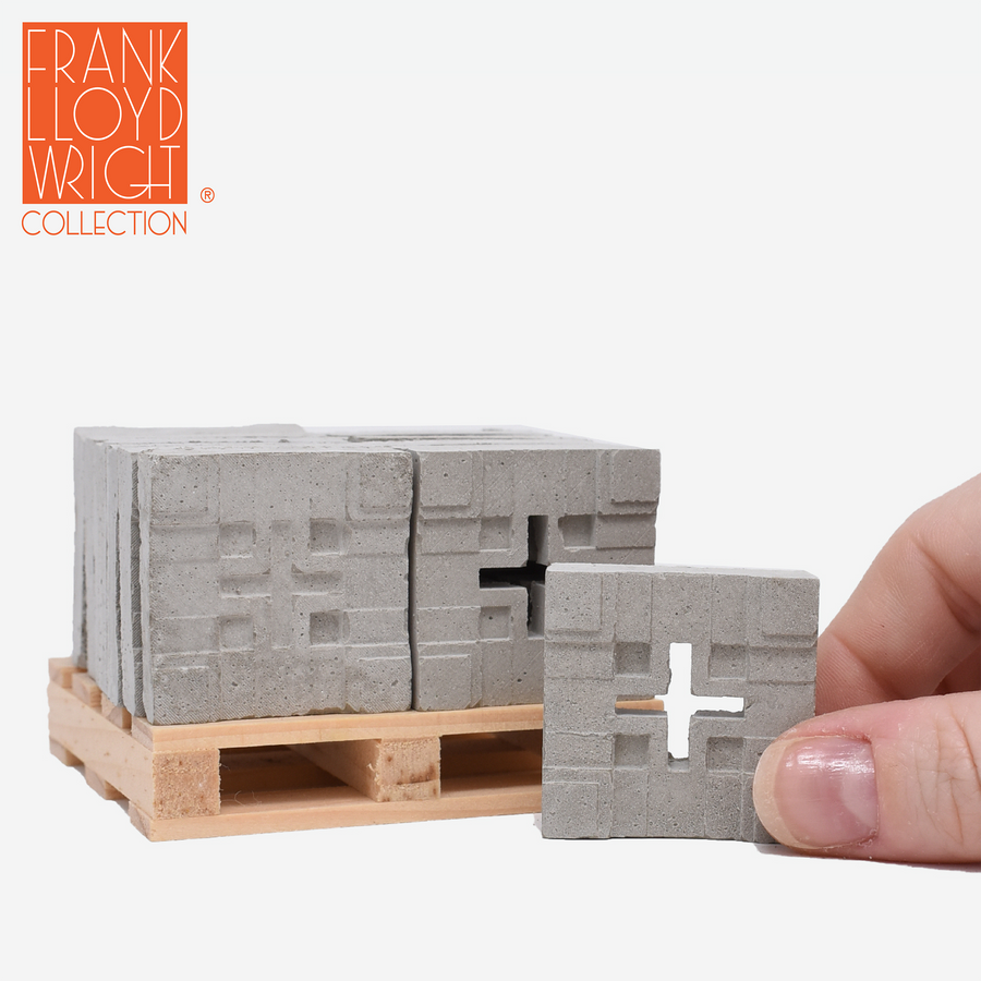 1:12 scale mini concrete textile blocks that mimic the frank lloyd wright millard house textile blocks on a mini wood pallet with a hand holding one in front of the pallet to show scale.
