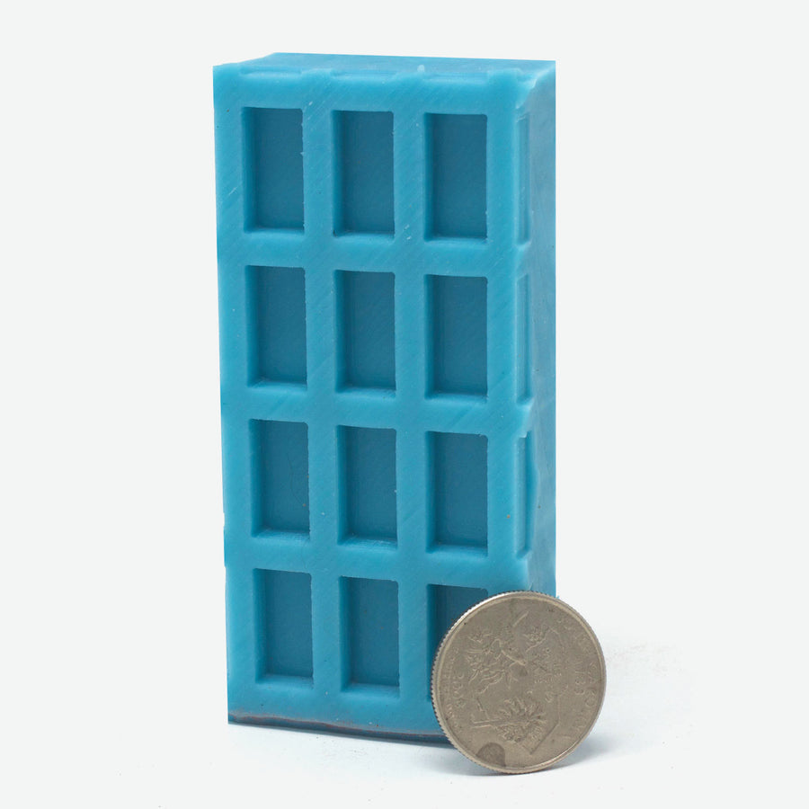 A 3x4 mold of 1:12 scale red brick pavers made of turquoise silicone standing vertically. A quarter rests against it for scale.