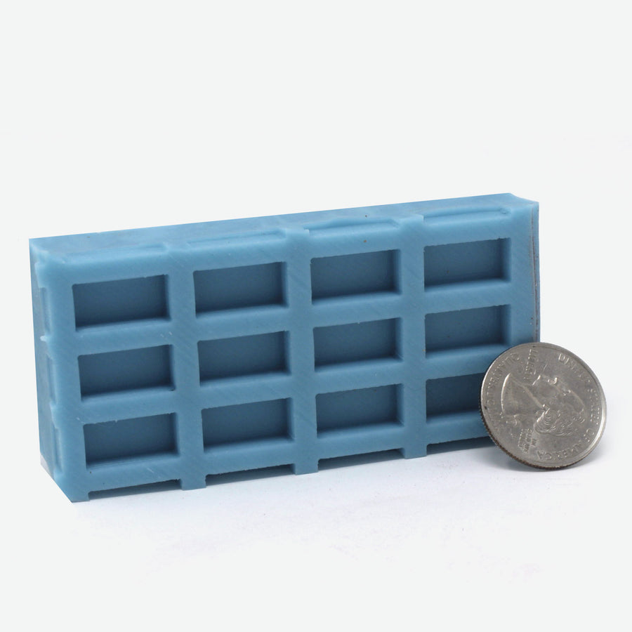A 3x4 mold of 1:12 scale red brick pavers made of turquoise silicone standing horizontally. A quarter rests against it for scale.