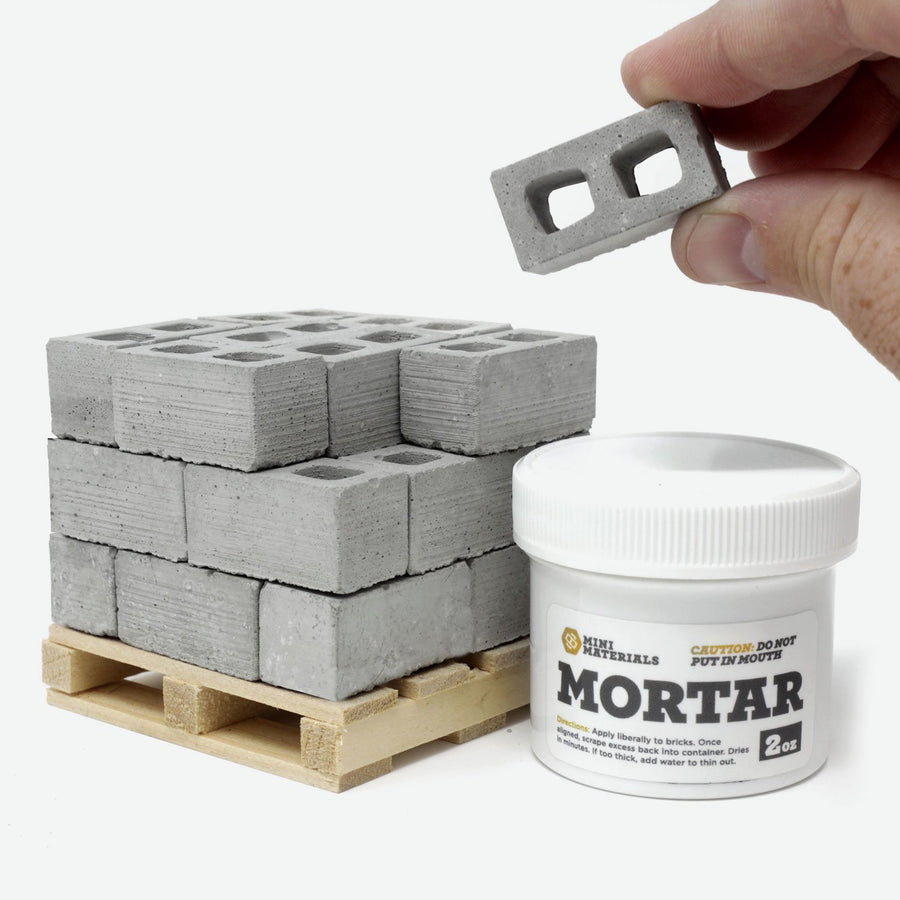 A pallet of 1:12 scale cinder blocks on a pine pallet with a white jar of mortar next to it. A hand is holding up one of the blocks.