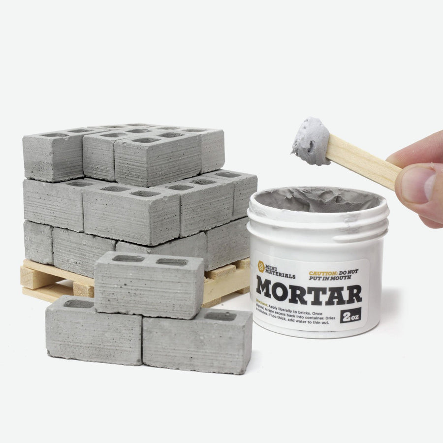 A pallet of 1:12 scale cinder blocks on a pine pallet with a white jar of mortar next to it. A hand is holding a stick with the mortar on it. The lid is laying next to it.