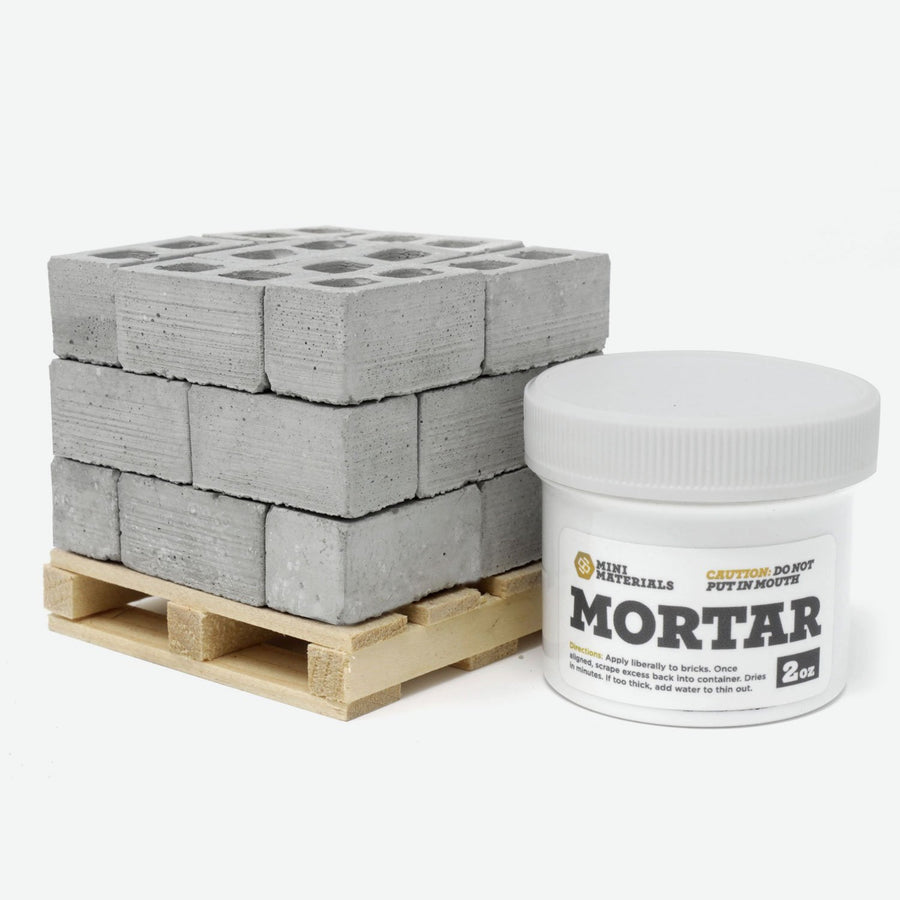A pallet of 1:12 scale cinder blocks on a pine pallet with a white jar of mortar next to it.