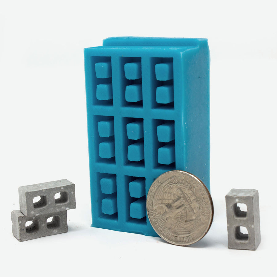 1:24 scale mini cinder block mold in turquoise with a quarter for scale.