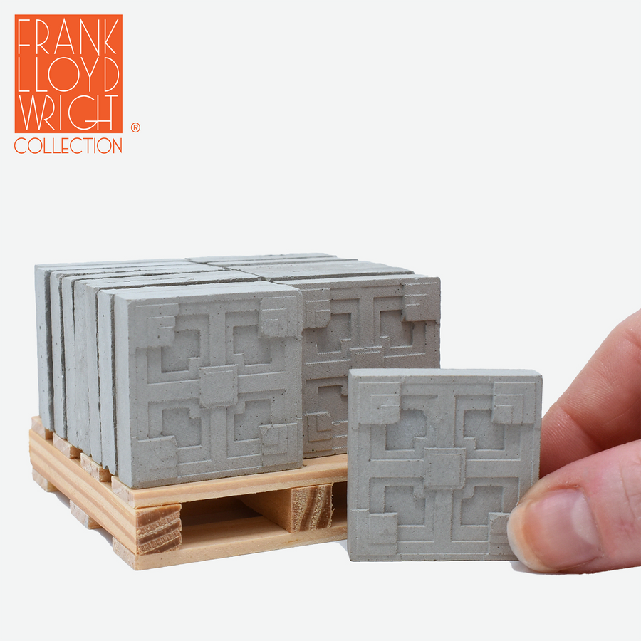 1:12 scale mini concrete textile blocks that mimic the frank lloyd wright storer house textile blocks on a mini wood pallet with a hand holding one in front of the pallet to show scale.