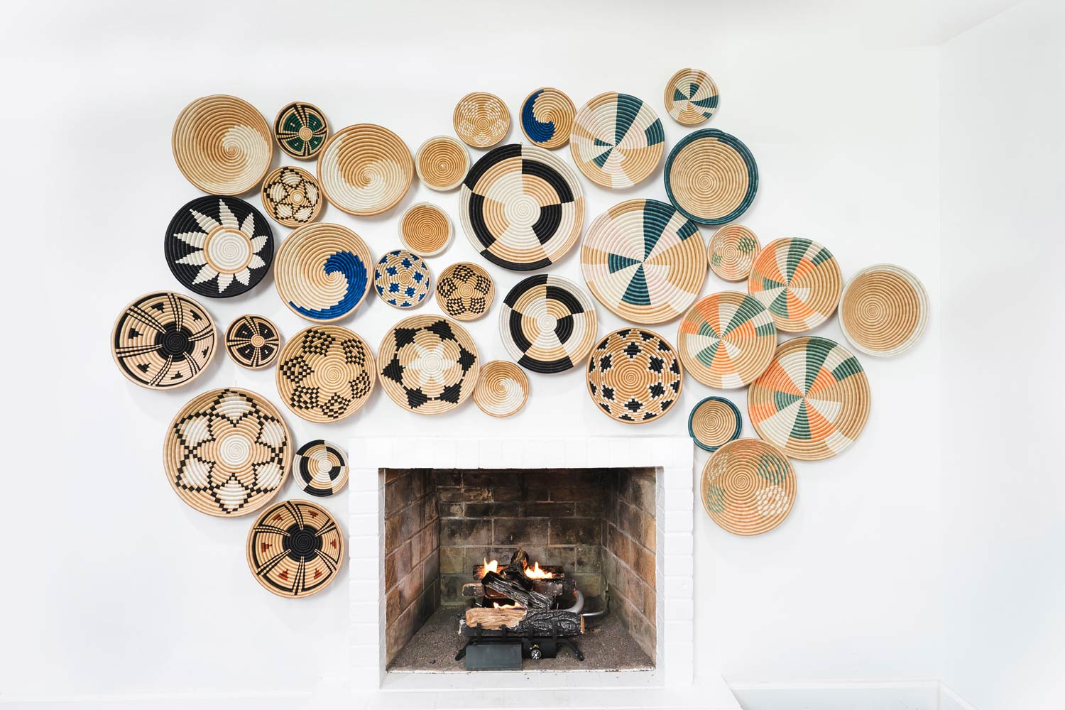 Large display of Local and Lejos bowls on a white wall above a fireplace.