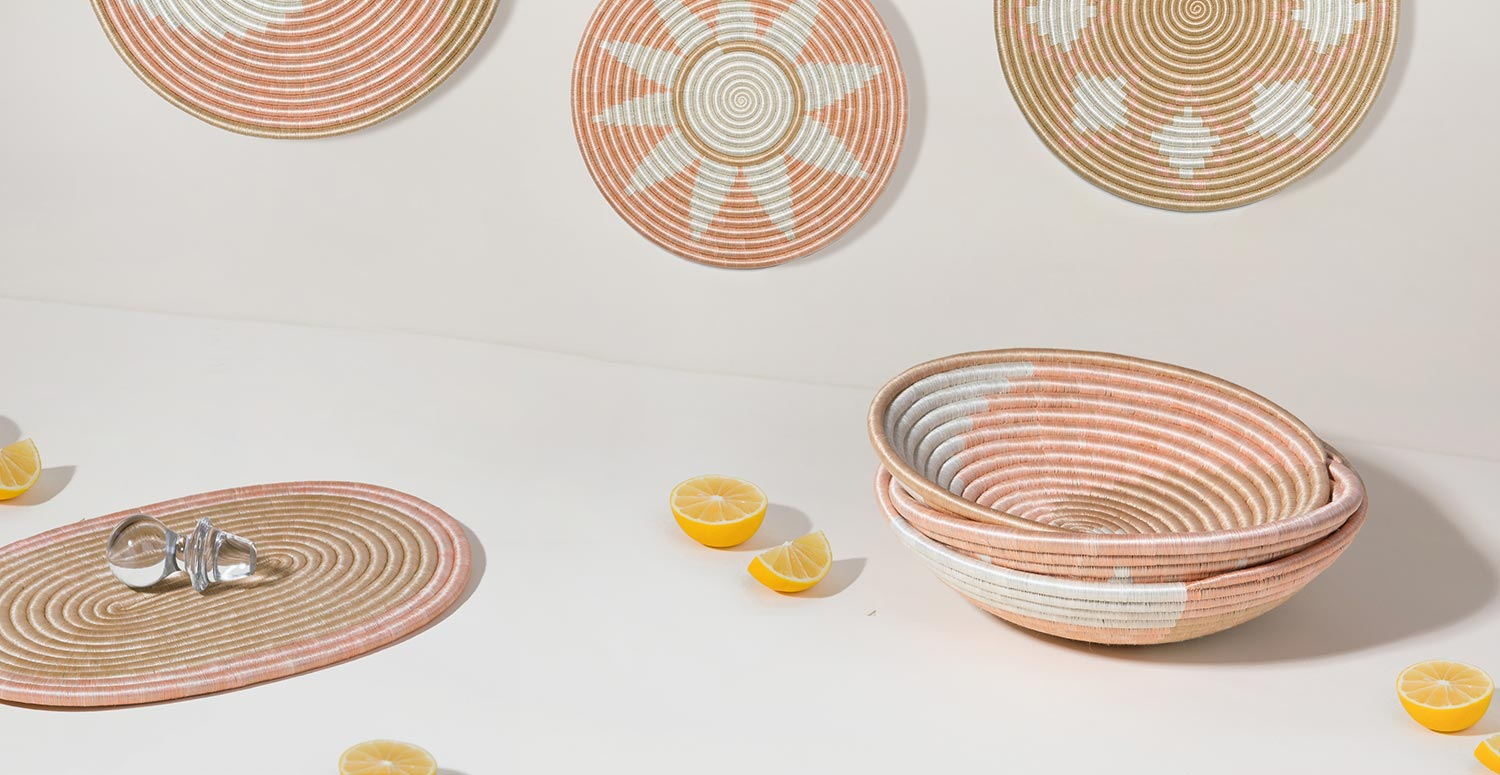 The Blush Collection bowls and flat circles sitting on a light tan background with bright lemons sitting by them for fun.