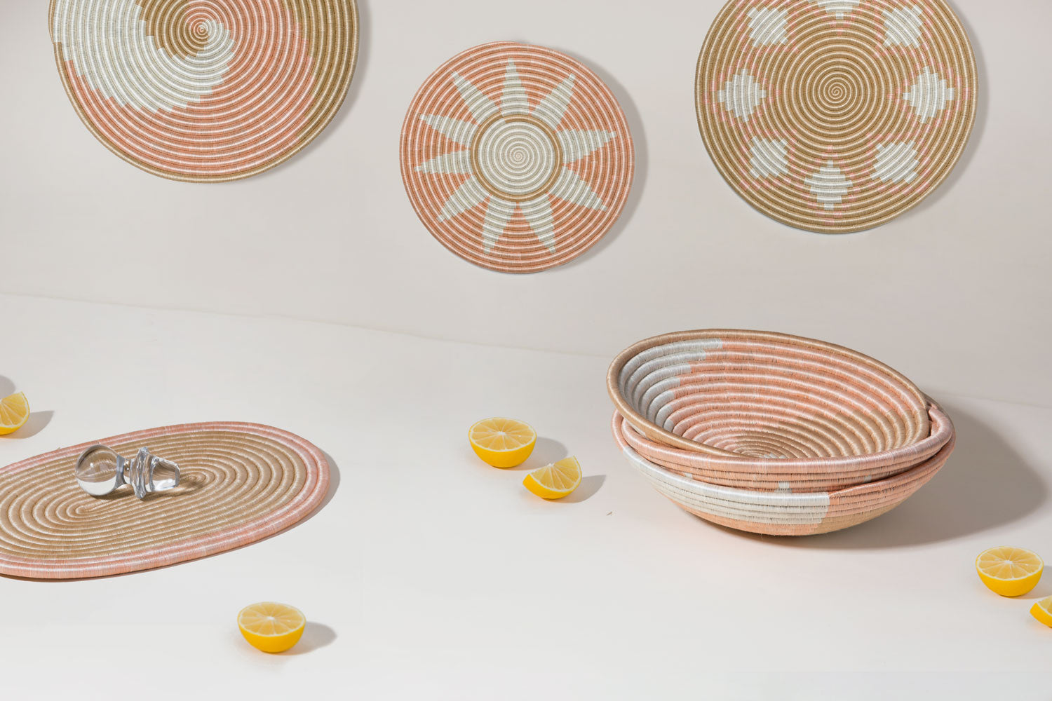 Pieces from the Blush Collection sitting on a tan background with bright yellow lemons surrounding the bowls and flat circles and flat ovals.