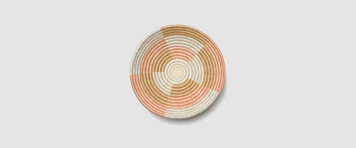 The blush, white and tea colored Staccato bowl against a light tan background.