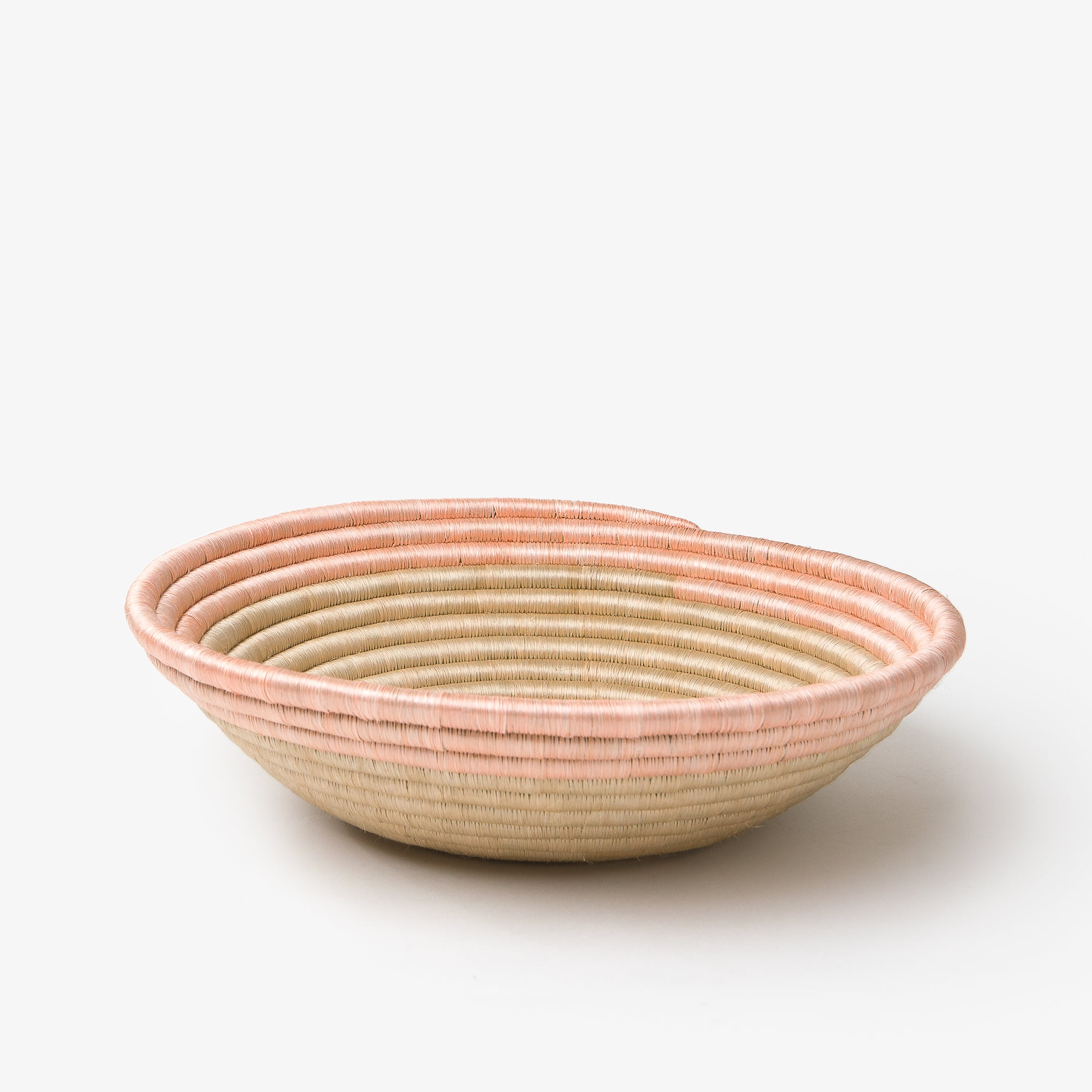 The Aura Bowl in blush on a grey background, shop from the side.