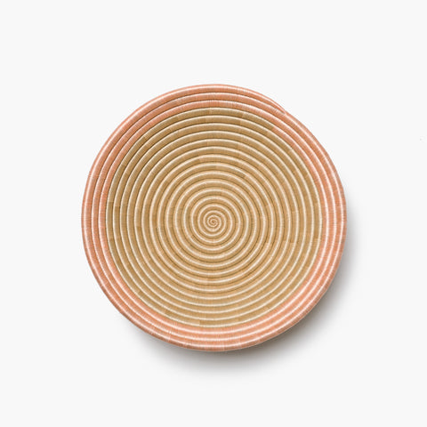 The Aura Bowl in blush on a grey background, shop from overhead.
