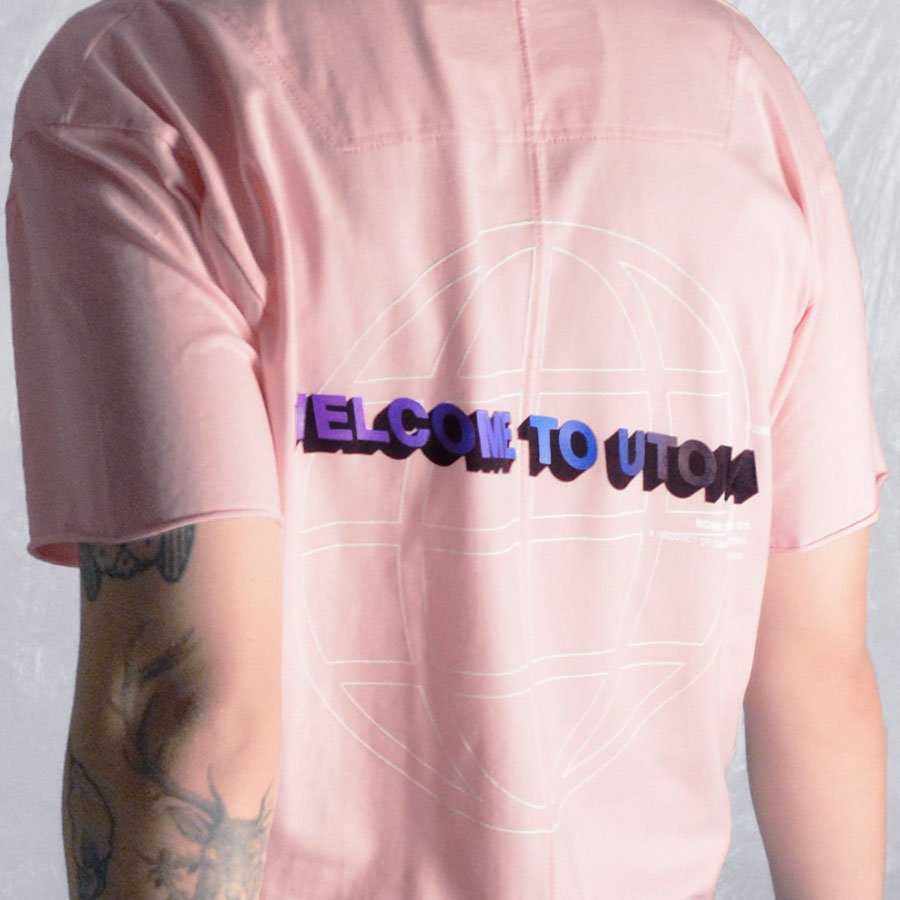 Wearing shot of Welcome to Utopia tshirt in soft pink