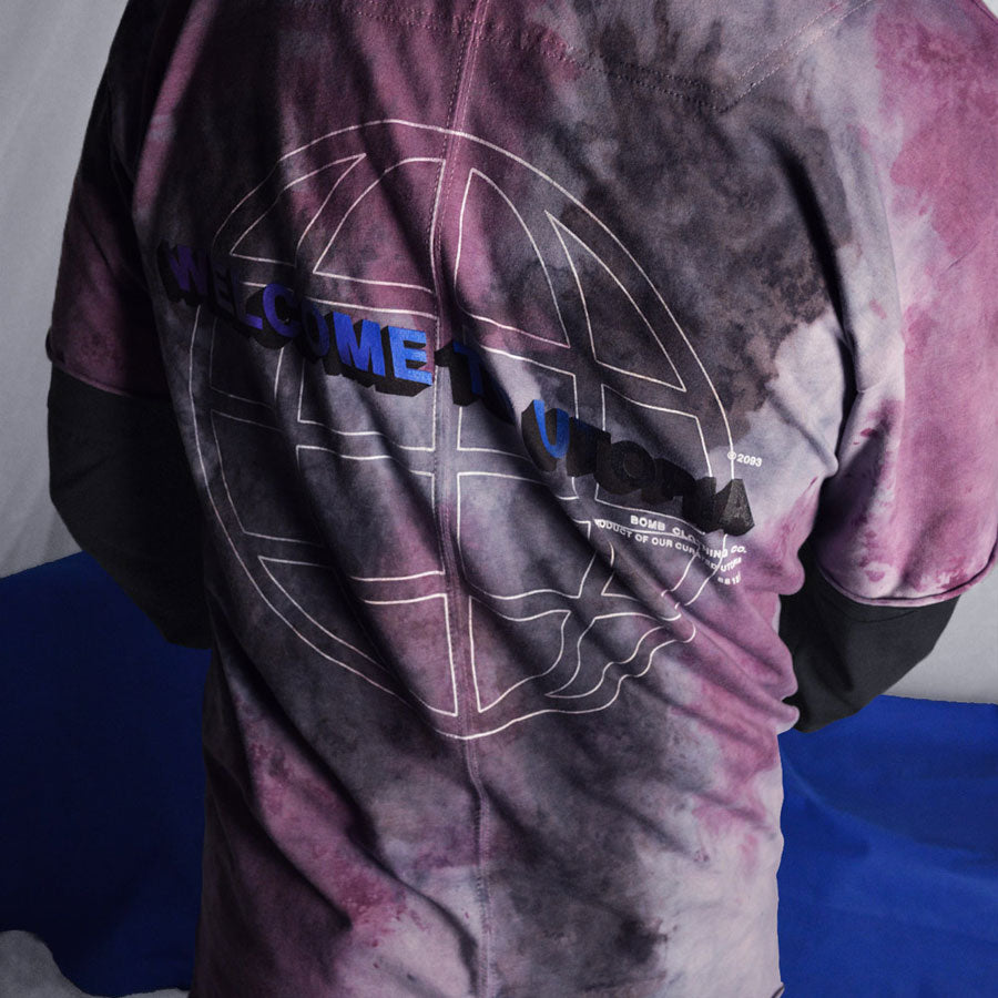 Detailed wearing shot of back Welcome to Utopia screen print on hand dyed tshirt in purple