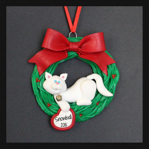 Cat holding on a Holly Wreath