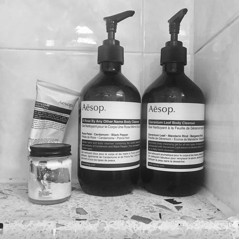Aesop shower gel bottles and facewash tube in monochrome bathroom shelf