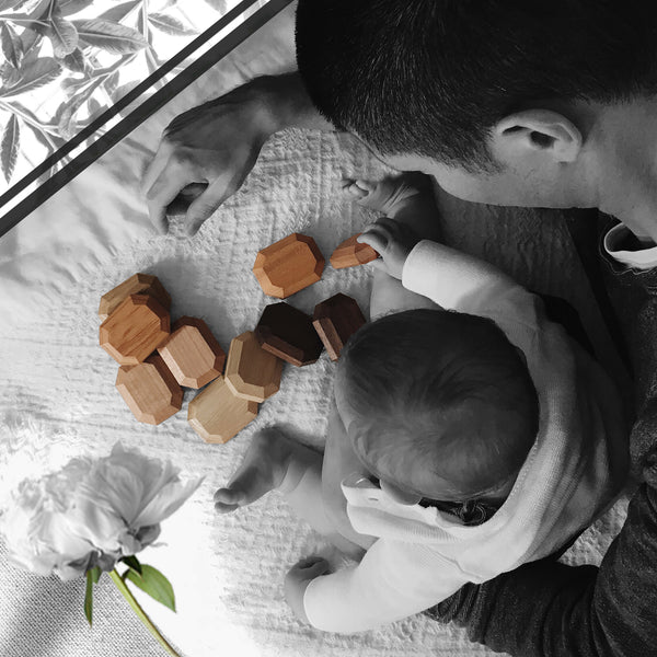 Father and baby with wooden toy flower and greenery as viewed from above
