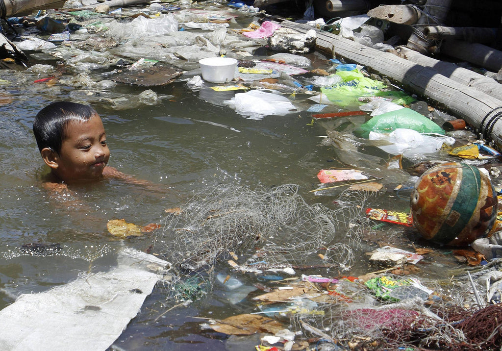 Boy swimming in plastic pollution and toxic plastic toys