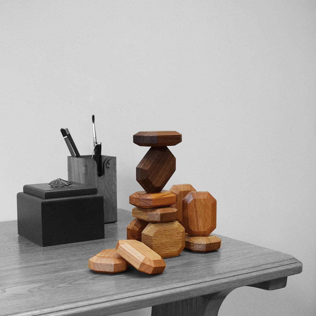4 types of sustainable wooden gems arranged in a stack on a desk