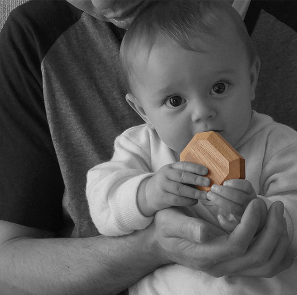 father with baby looking forward and holding wooden gem