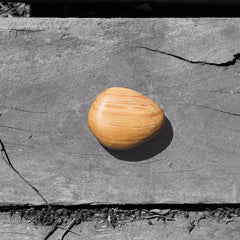 single smooth organic pebble on wooden slate background