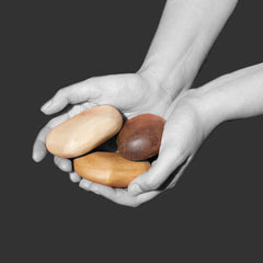 wooden pebbles in three types of wood in hands