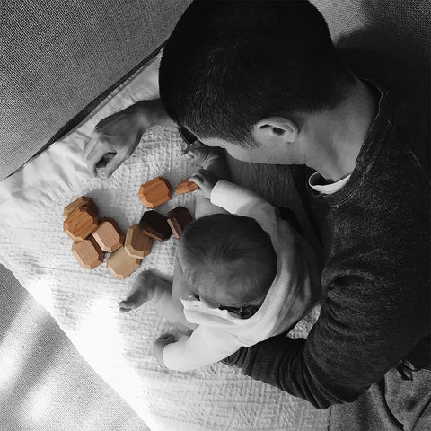 dad and baby with twoodies in wood stacked on the floor
