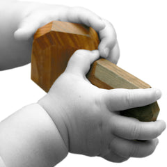 baby hands clasp wooden blocks to develop fine motor skills