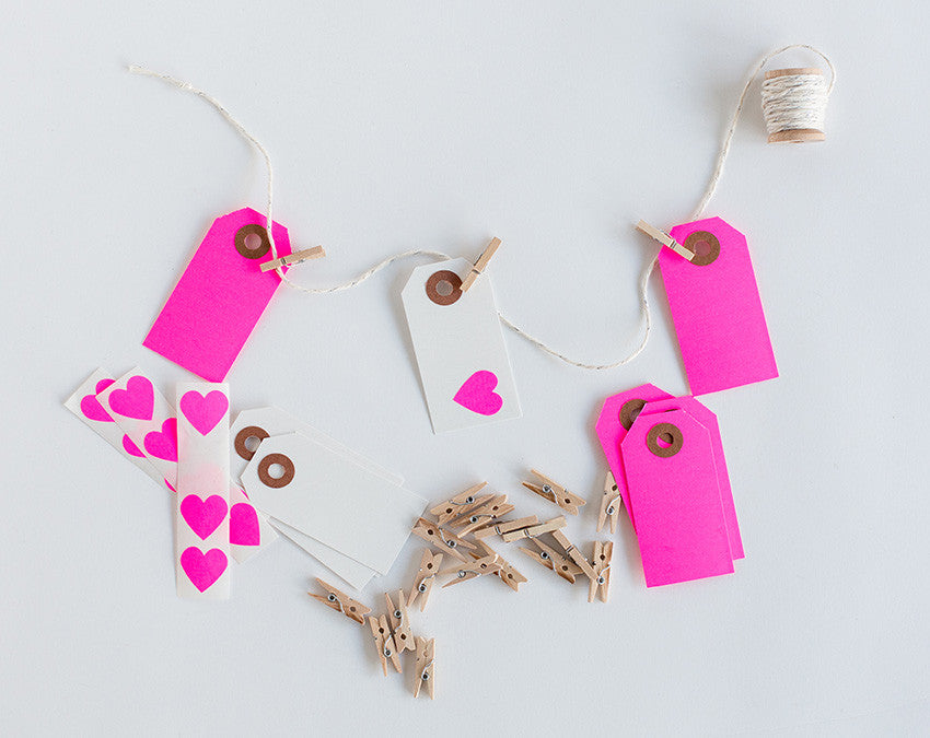 Neon pink garland decorating kit by Knot & Bow. Kit contains 20x mini wooden clothes pegs, 5 yards of glitter twine, 5 parcel tags, 5 white tags and 12 heart stickers.