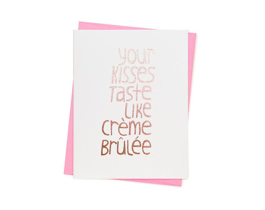 Card reads 'YOUR KISSES TASTE LIKE CRÈME BRÛLÉE'. Letterpressed gold ink on luxury cotton paper. Blank inside with fluorescent pink envelope. By Ashkahn.