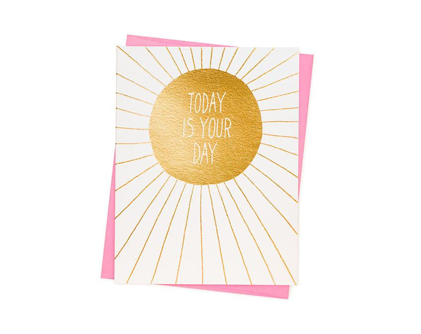 Card reads 'TODAY IS YOUR DAY' inside sun illustration with handwritten font. Letterpressed gold ink on luxury cotton paper. Blank inside with fluorescent pink envelope. By Ashkahn.