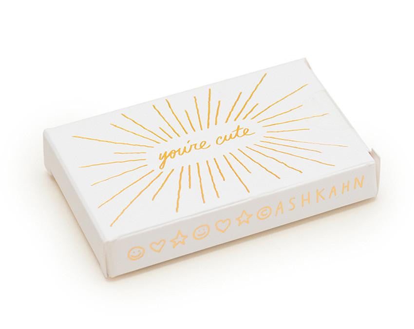 25 mini compliment card set reads 'you're cute' in handwritten font. Letterpressed gold ink on luxury cotton paper. By Ashkahn.