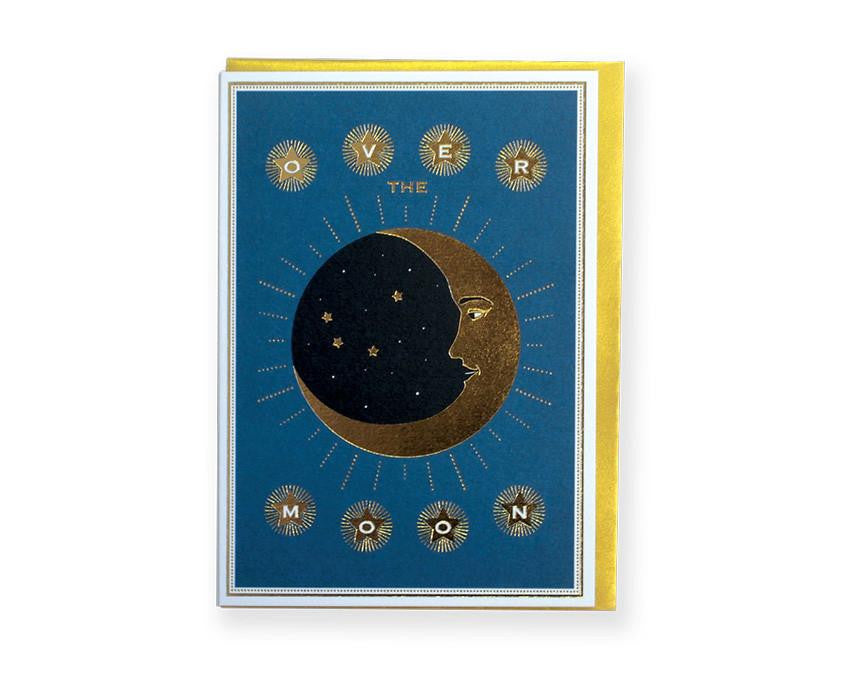 Premium greeting card from Chase and Wonder. Tarot card illustration of moon and stars, reads 'over the moon' in teal and black colour with gold foil. Printed on 320gsm rives card, blank inside paired with a gold envelope.