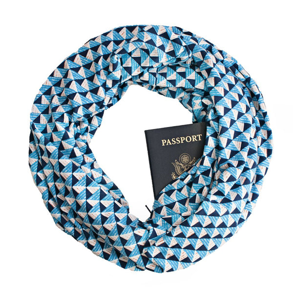 A rayon jersey travel scarf with a hidden zippered pocket that haas blue geo print.