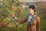 A young girl picking apples in New England wearing a summer floral rayon secret pocket travel scarf.