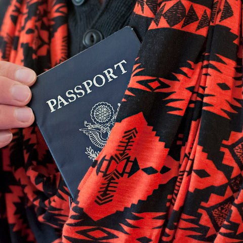 An orange and black infinity loop pocket scarf with passport being placed into the pocket.