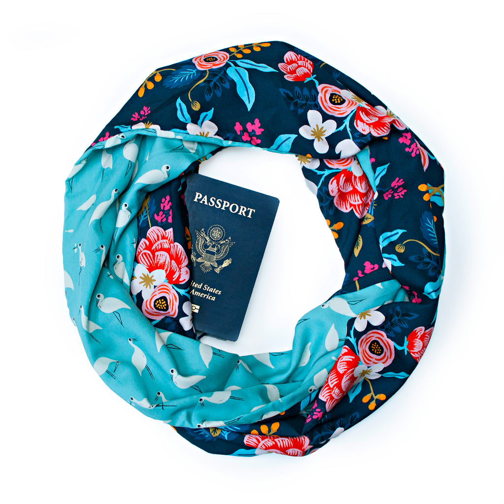 A lightweight floral rayon travel scarf with a passport coming out of the secret zippered pocket.