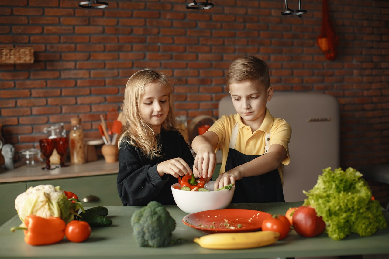 Kids in the kitchen cooking with veggies
