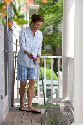 Woman cleaning deck with hose