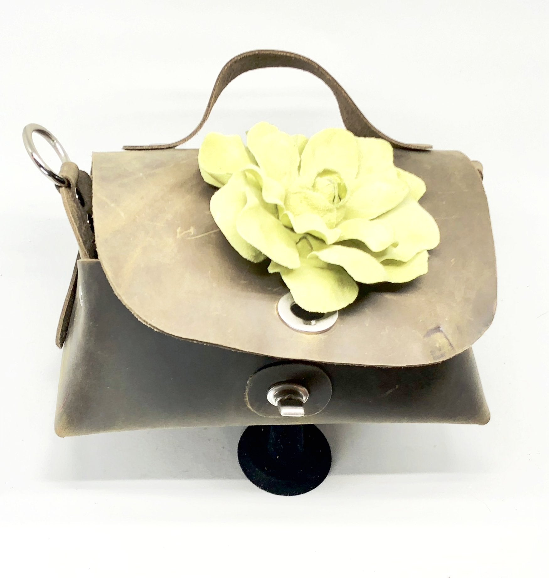 LEATHER RIVETED BAG WITH METAL HARDWARE, ADJUSTABLE SHOULDER STRAP AND OVERSIZED SUEDE FLOWER by nyet jewelry