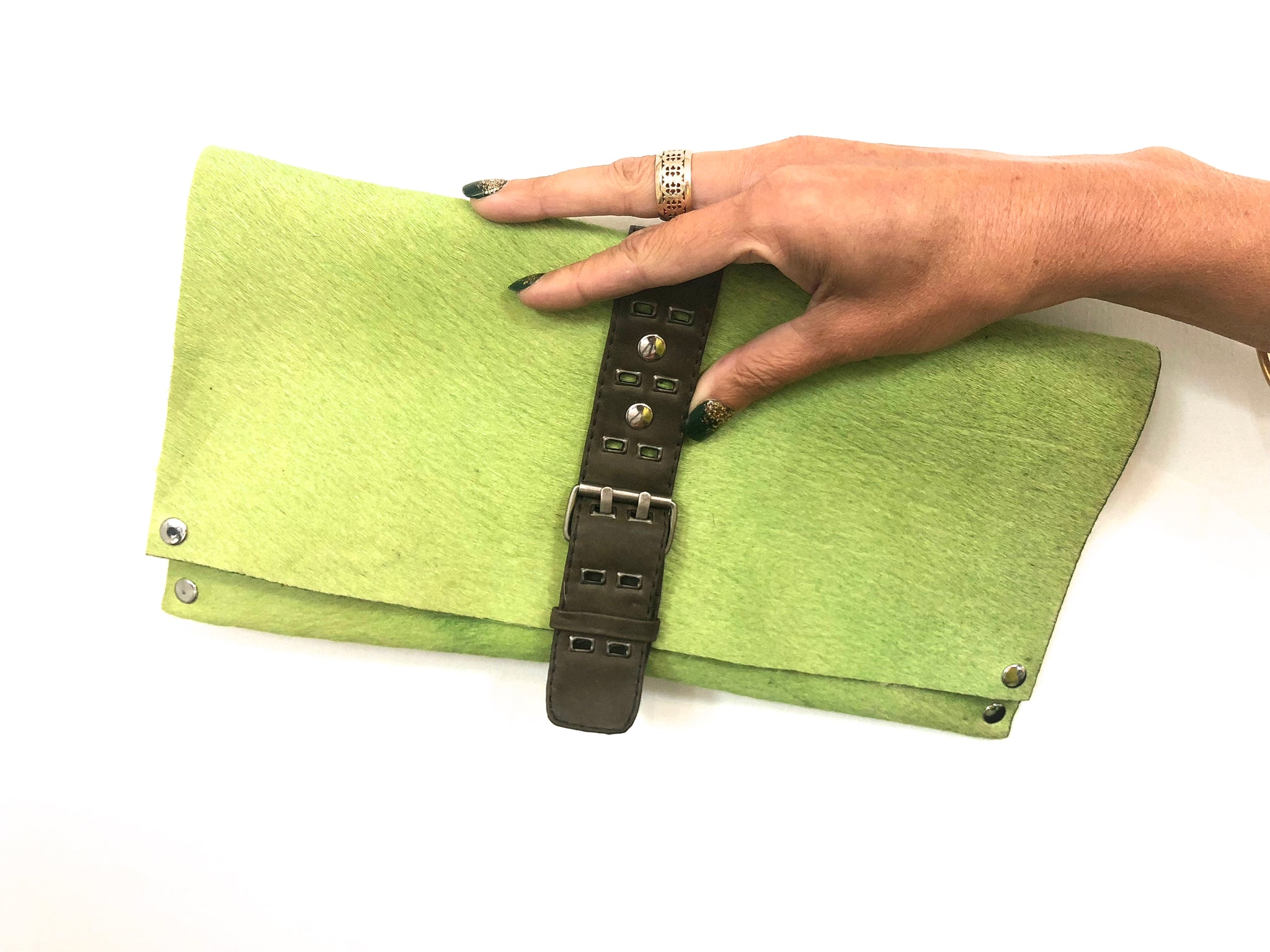 GREEN HAIR-ON COWHIDE CLUTCH WITH DETAILED UTILITY LEATHER STRAP AND BELT BUCKLE-STYLE CLOSURE by nyet jewelry