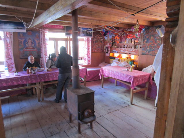 Typical lodge dining room ringed by tables and a wood-burning stove in centre