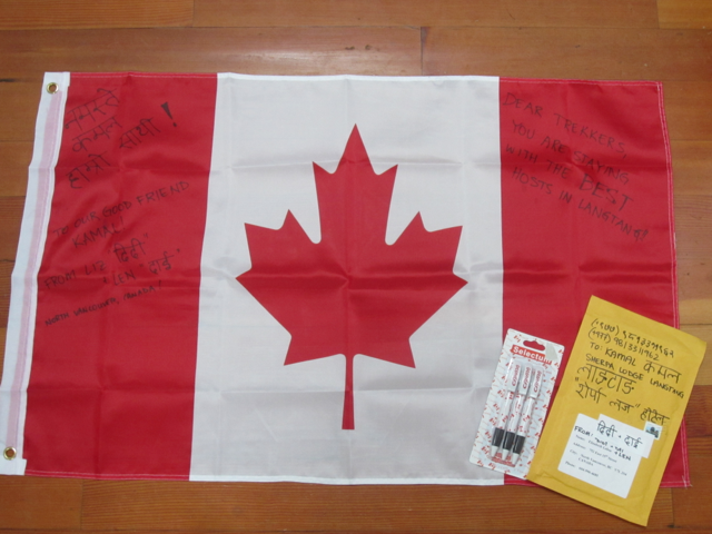Small Canadian flag with Nepali and English writing on it beside the parcel to be delivered by hand