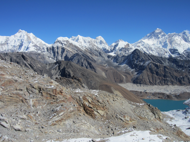 Mount Everest seen in the distance from a high mountain pass across a valley
